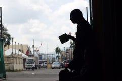 Blinder alter männlicher Bettler, der suchende Almosen des Wasserschöpflöffels an den Kirchenportalruinen hält Schattenbilder Stockbild