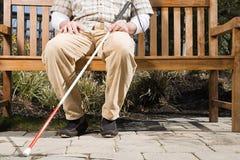 Blinder, der auf einer Bank sitzt Stockbild