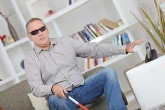 Blinder, der auf Sofa sitzt Lizenzfreies Stockfoto