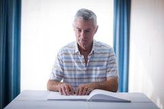 Blinder, der ein Blindenschrift-Buch liest Lizenzfreie Stockbilder
