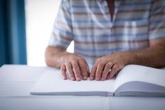 Blinder, der ein Blindenschrift-Buch liest Stockfotos