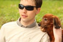 Blinder junger Mann mit Hundanleitung Stockbild