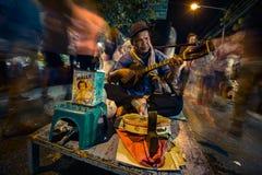 Blinder spielt mehrfache Instrumente für Spenden auf Straße am Nachtmarkt Lizenzfreie Stockfotos