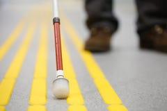 Blindes Fußgängergehen auf der Tastpflasterung Stockfoto