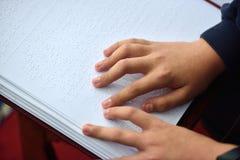 Blindes Kind las das Buch, das in Blindenschrift geschrieben wurde Lizenzfreie Stockbilder