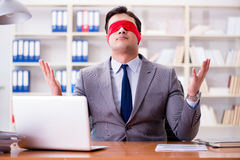 The blindfold businessman sitting at desk in office Royalty Free Stock Photos