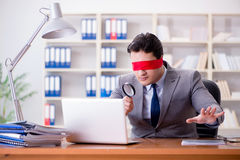 The blindfold businessman sitting at desk in office Stock Photography