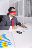 Blindfold businessman working with his laptop Royalty Free Stock Photo