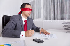 Blindfold businessman working with his laptop Royalty Free Stock Photos