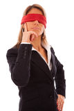 Blindfold businesswoman thinking. Businesswoman with a red scarf in her eyes, thinking what to do Stock Photography