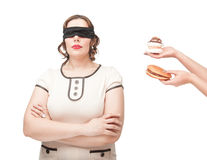 Blindfold plus size woman temptating with junk food. Blindfold beautiful brunette plus size woman temptating with junk food isolated Stock Image