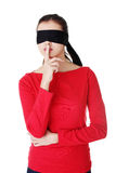 Blindfold woman with finger on lips. Stock Photo