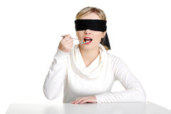 Blindfold woman holding spoon with pile of pills Stock Image