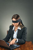 Blindfolded business woman with laptop Royalty Free Stock Image