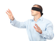 Blindfolded businessman. Businessman blindfolded stretching his arms out, isolated on white background Royalty Free Stock Image
