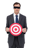 Blindfolded businessman holding a red target Royalty Free Stock Photography