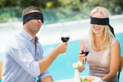 Blindfolded couple holding red wine Stock Images