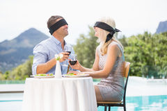 Blindfolded couple holding red wine while sitting by swimming pool Royalty Free Stock Photo