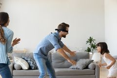 Blindfolded father playing hide and seek game with family at hom. E, cute child daughter runs from dad having fun, parents kid girl laughing spending time royalty free stock images