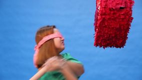 Blindfolded girl beats a toy heart with her hands. HD stock video footage