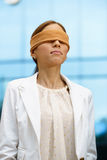 Blindfolded hispanic business woman near office building Stock Image