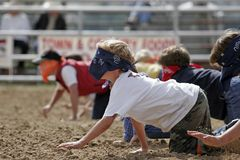 Blindfolded Kids Having Fun. A group of blindfolded children race on their hands and knees at the start of a charity 'Watermelon Crawl' in small town, rural royalty free stock photos