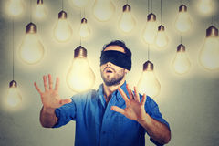 Blindfolded man walking through light bulbs searching for bright idea. Blindfolded young man walking through light bulbs searching for bright idea royalty free stock photo