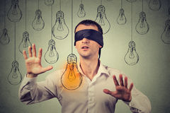 Blindfolded man walking through light bulbs searching for bright idea Royalty Free Stock Photography