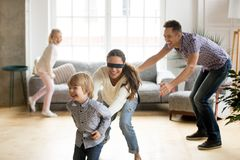 Blindfolded mother catching son playing hide and seek with famil. Blindfolded mother catching little son playing hide and seek at home, happy children having fun royalty free stock image