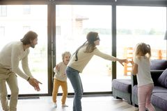 Blindfolded mother playing hide and seek game with father kids Royalty Free Stock Photo