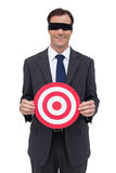 Blindfolded and smiling businessman holding a red target Royalty Free Stock Image