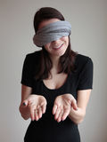 Blindfolded woman showing palms. Blindfolded young woman showing palms isolated on grey background Stock Image