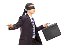 Blindfolded young businessman with briefcase royalty free stock photography