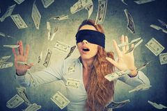 Blindfolded young entrepreneur  businesswoman trying to catch dollar bills Stock Image