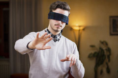 Blindfolded young man at home in living room cannot see Stock Photo