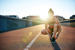 Blinding sun shines over should of woman jogger. As she kneels to tie her running shoes royalty free stock photos