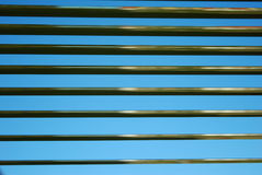 Blinds background. Metallic blinds on a blue sky. Window Royalty Free Stock Photo