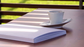 Blinds on pavilion throw shadow over a table with magazine and coffee cup stock video footage