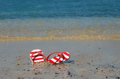 Blingy Flip Flops. Sit on the sands of Anaehoomalu Bay on the Big Island of Hawaii. Sandals are red and white with white rhinestones along thong edge royalty free stock photo