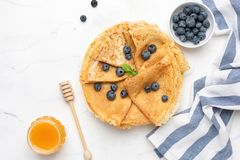 Blini or crepes with fresh berries and honey royalty free stock photography