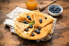 Blini or crepes with fresh blueberries and honey stock photos