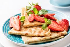 Blini or crepes with strawberry. On a blue plate, closeup view. Tasty thin pancakes for breakfast or dessert served with fresh red berries stock photography
