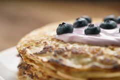Blini or crepes with yogurt and blueberries closeup. Sweet breakfast royalty free stock photography