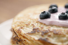 Blini or crepes with yogurt and blueberries closeup Stock Photos