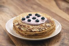 Blini or crepes with yogurt and blueberries closeup. Sweet breakfast stock images
