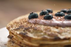 Blini or crepes with yogurt and blueberries closeup. Sweet breakfast royalty free stock photo
