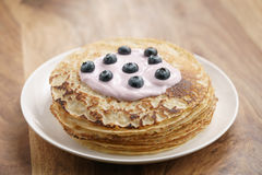 Blini or crepes with yogurt and blueberries on wood table Stock Photo