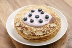 Blini or crepes with yogurt and blueberries on wood table Stock Photos