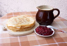 Blini with milk and berry jelly. Still Life with stack of pancakes , a jug of milk and berry jelly Royalty Free Stock Photos