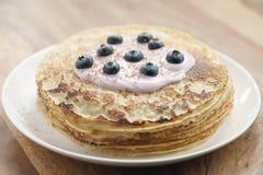Blini mit Jogurt und Blaubeeren auf hölzerner Tabelle Stockfoto